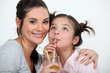 Mother and daughter drinking through straws
