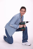 portrait of cute brunette holding electric drill
