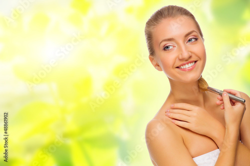 Young woman with makeup brush on spring background