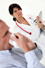 Doctor writing on a clipboard as her patient blows his nose