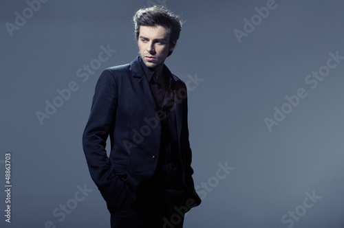 Portrait of a young business man leaning against the wall