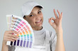 Painter giving the a-ok sign and holding a palette of colors