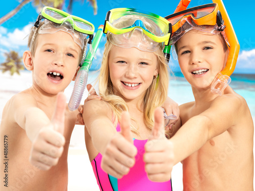 Happy children with thumbs-up gesture at beach