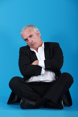 middle-aged man sitting cross-legged