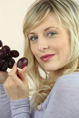 Blond woman eating bunch of grapes