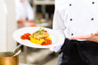 Female Chef in restaurant kitchen presenting dish