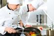 Two chefs in hotel or restaurant kitchen