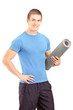 A male athlete holding an exercising mat
