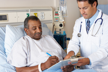 Doctor Explaining Consent Form To Senior Patient