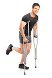 Injured young male athlete walking with crutches