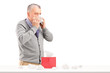 Man blowing nose with a box of tissues on a table