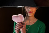 Teenage girl holding a pink heart  under her umbrella
