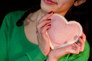 Teenage girl holding a pink heart