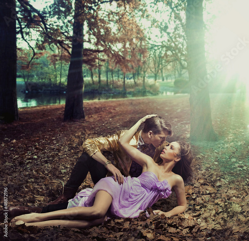 A loving couple lying on autumn leaves