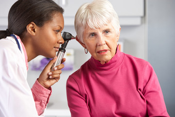 Doctor Examining Senior Female Patient's Ears