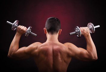 Muscular young man lifting weights against black background