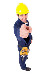 Full lenght of a smiling young builder pointing, isolated on whi