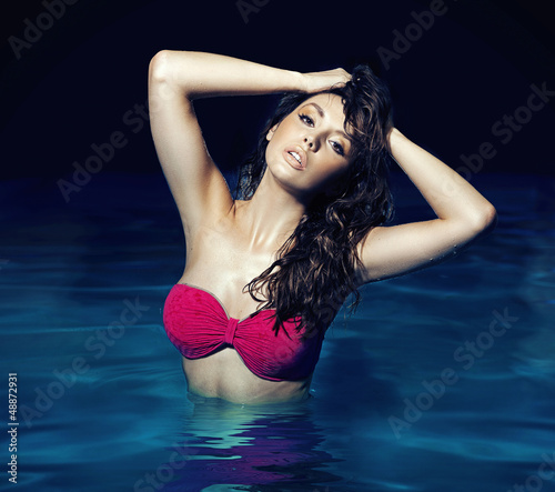 Sensual brunette posing in the swimming-pool