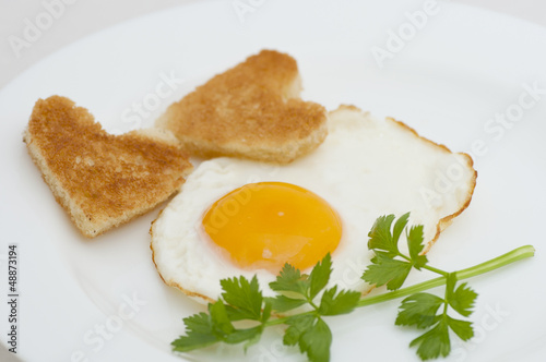 Fried egg with heart-shaped toasts for romantic breakfast