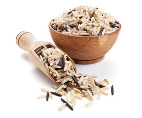 wild brown rice in a wooden bowl isolated on white