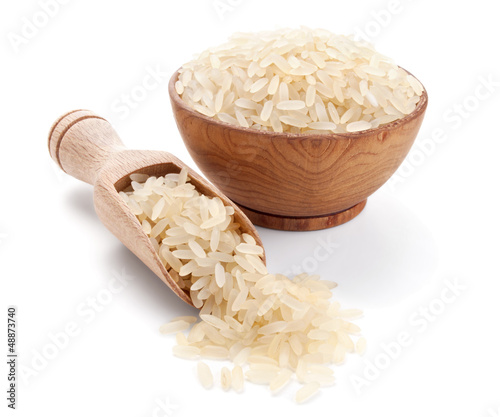parboiled rice in a wooden bowl isolated on white