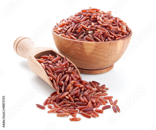 red rice in a wooden bowl isolated on white