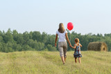 Mother and daughter go from the camera in ibeautiful field