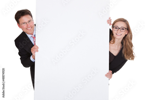 Professional man and woman with a blank sign