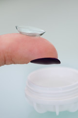 Female finger with a contact lens on it
