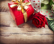 Valentine. Rose Flower and Gift Box over Wooden Background