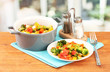 Vegetable stew in gray pot on wooden table on bright background