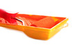 roller in tray with orange paint isolated on white