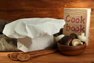 Composition with chef's hat on wooden background