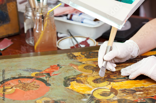 Restorer gilding on icon with agate burnisher