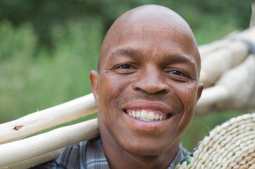 Smiling South African entrepreneur small business broom salesman