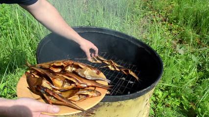 speed up hand take freshly smoked fish put wooden dish plate