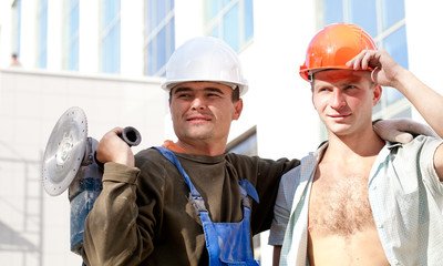 Two positive industrial workers on the building background
