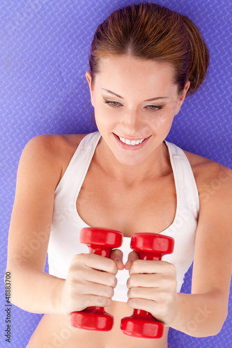woman laying on the floor and lifting dumbbells