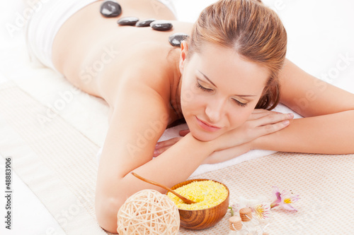 brunette woman receiving spa stones therapy