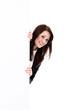 Geschäftsfrau blickt lächelnd hinter Wand hervor