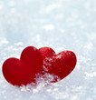 Two red frozen heart on snow
