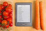 List of Recipes on a Tablet among Tomatoes and Carrots