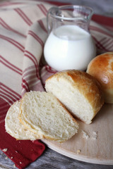 Milk buns bread with a milk pot on a kitchen towel