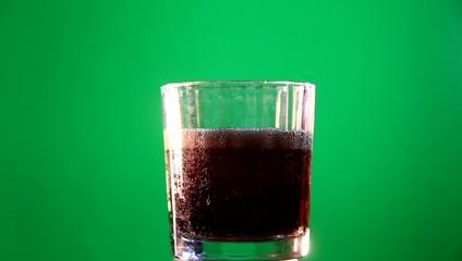 bevanda versata in bicchiere su sfondo verde