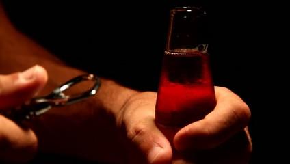 mani di uomo apre (stappa) bibita di vetro al buio