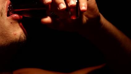 ragazzo beve succo o cocktail da bottiglia di vetro al buio
