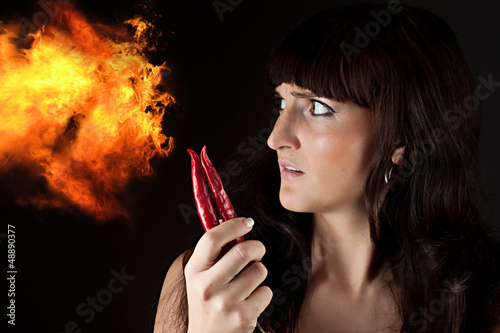 beautiful woman looking hot spicy chili pepper
