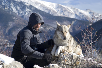 Man with dog hike in winter mountains