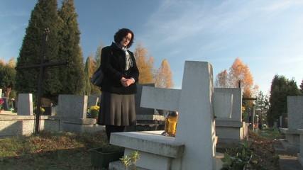 widow praying at a grave