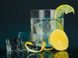 Ice cubes in glass with lemon on dark blue background